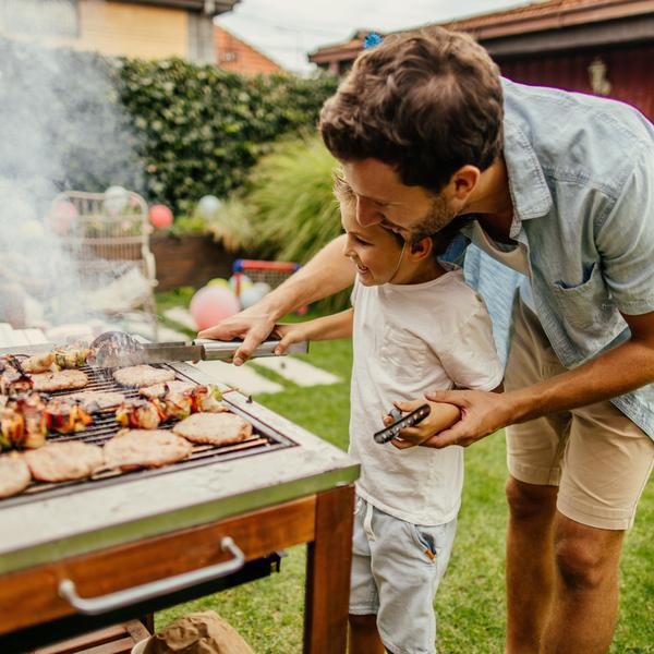 Photo of father and son grilling meat during the barbecue party in their yard