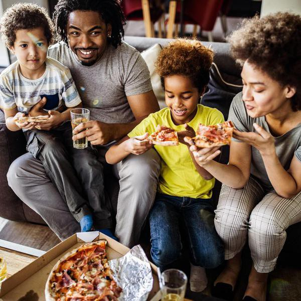 High angle view of happy African American family eating pizza for lunch in the living room.